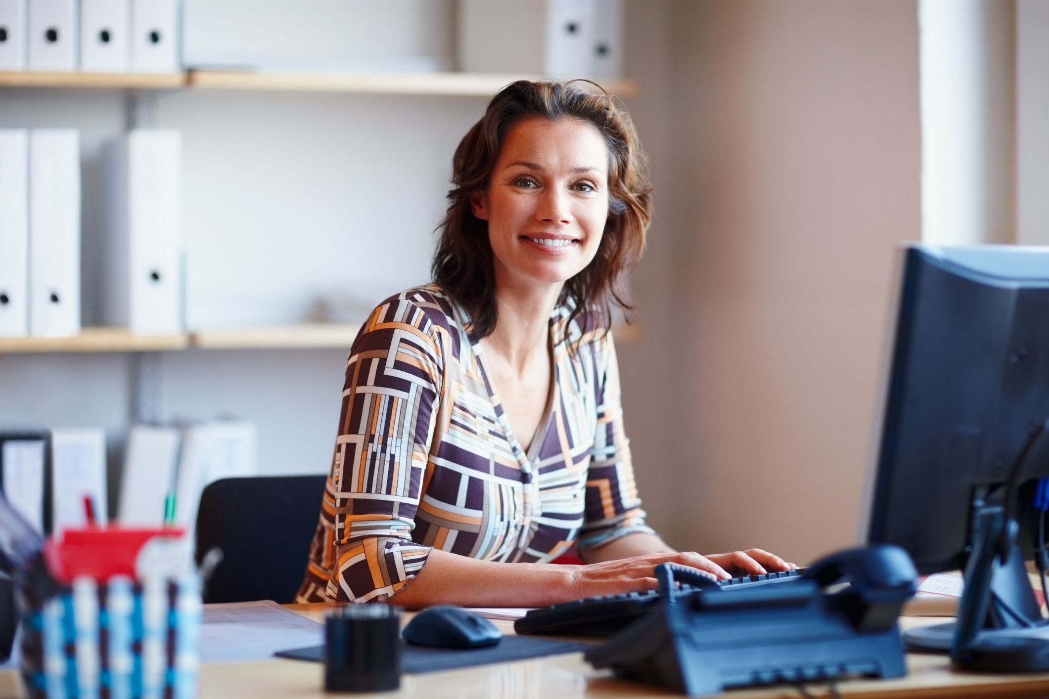 Portrait of a smiling mature businesswoman at office desk with a computer