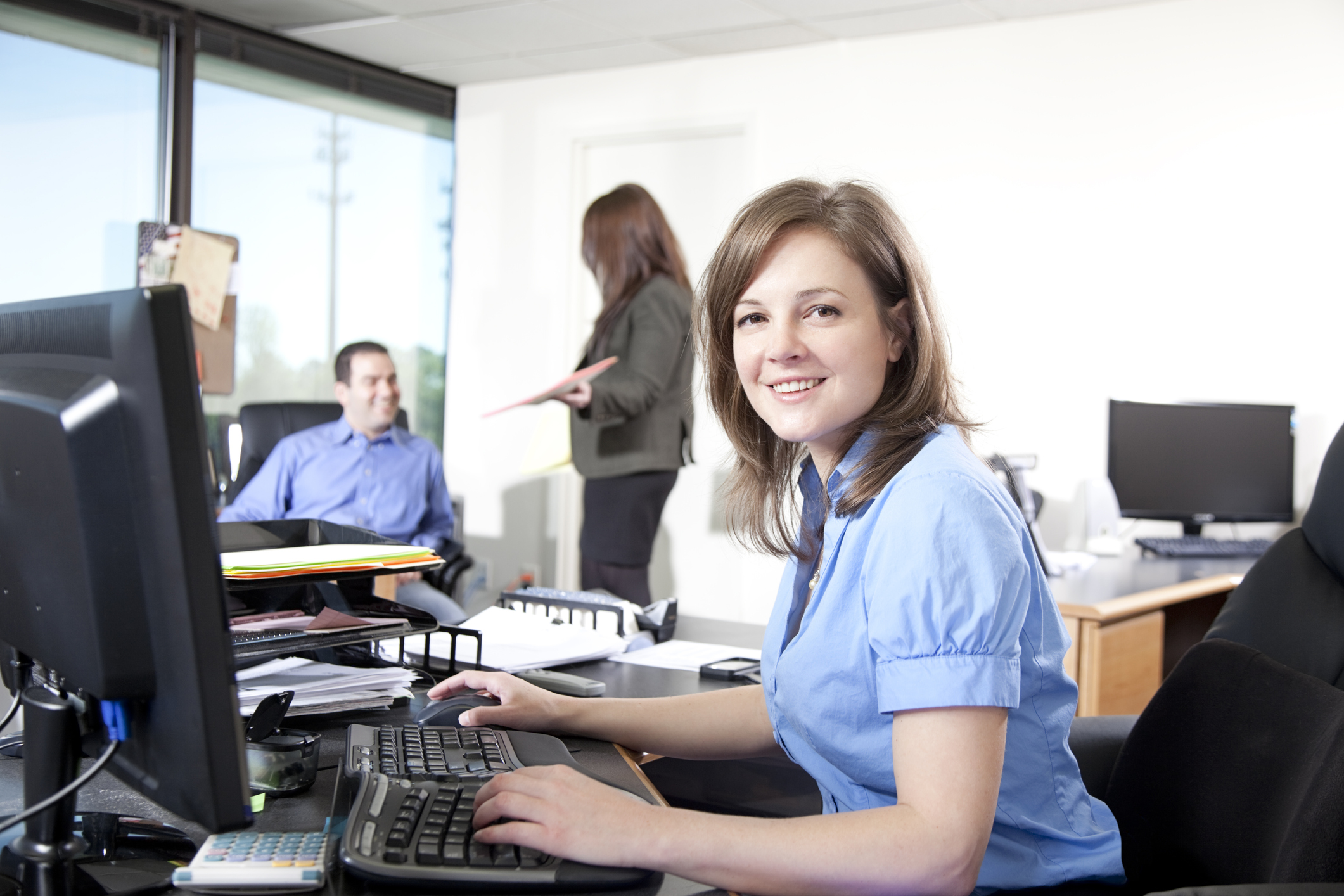 Smiling businesswoman with colleagues in the background