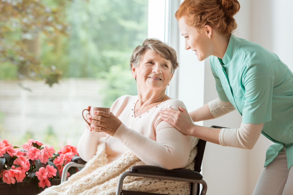 health care assistant helping elderly patient holding cup