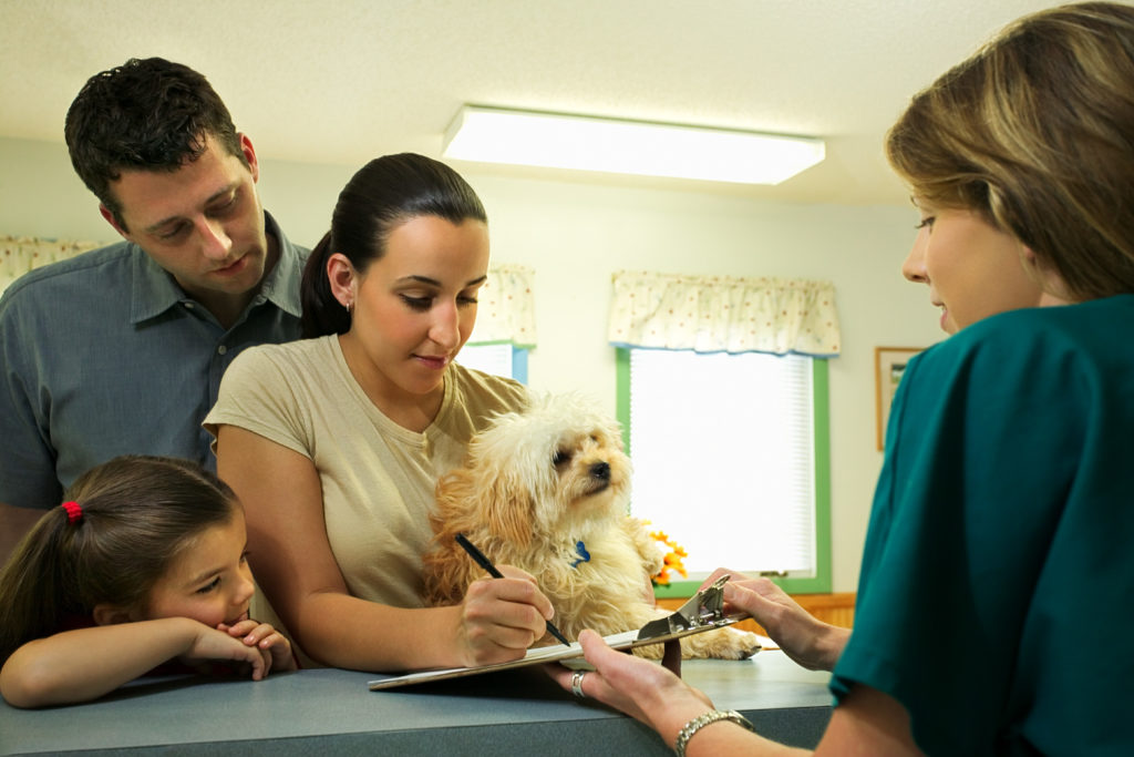 family registering their dog at a veterinary clinic/hospital