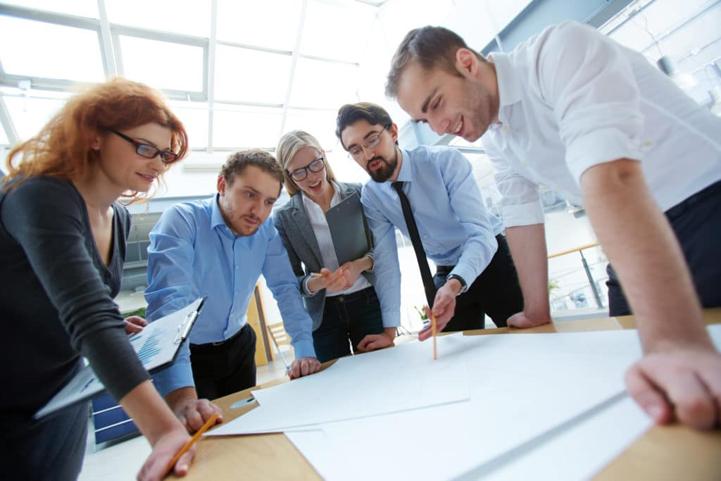 group of business people looking at plans together
