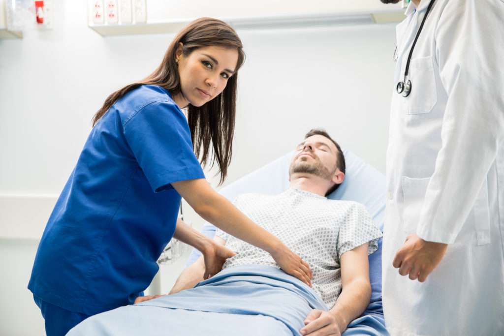 Portrait of a beautiful Hispanic doctor examining a patient in the emergency room and making eye contact