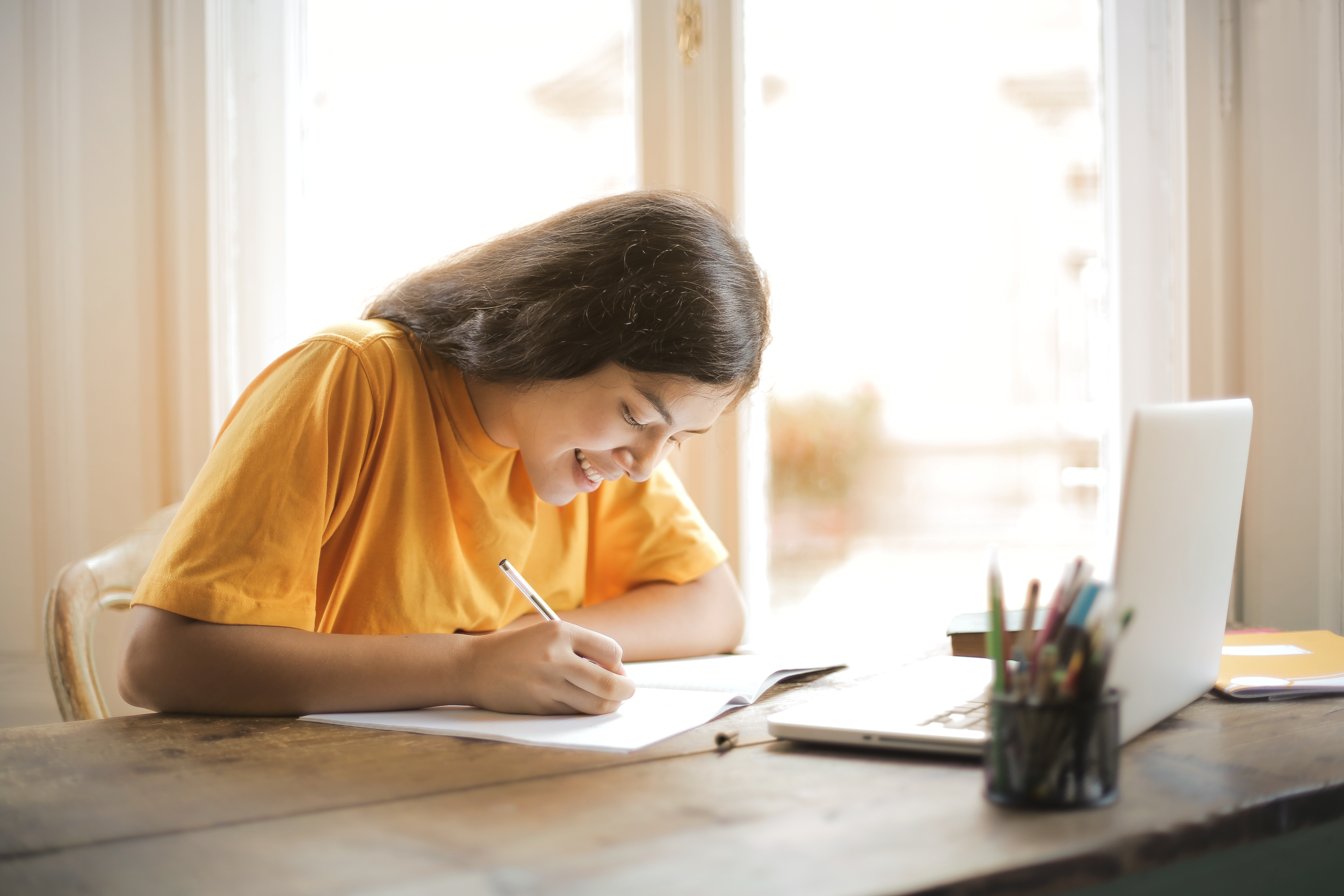 girl learning online at home on laptop and writing notes