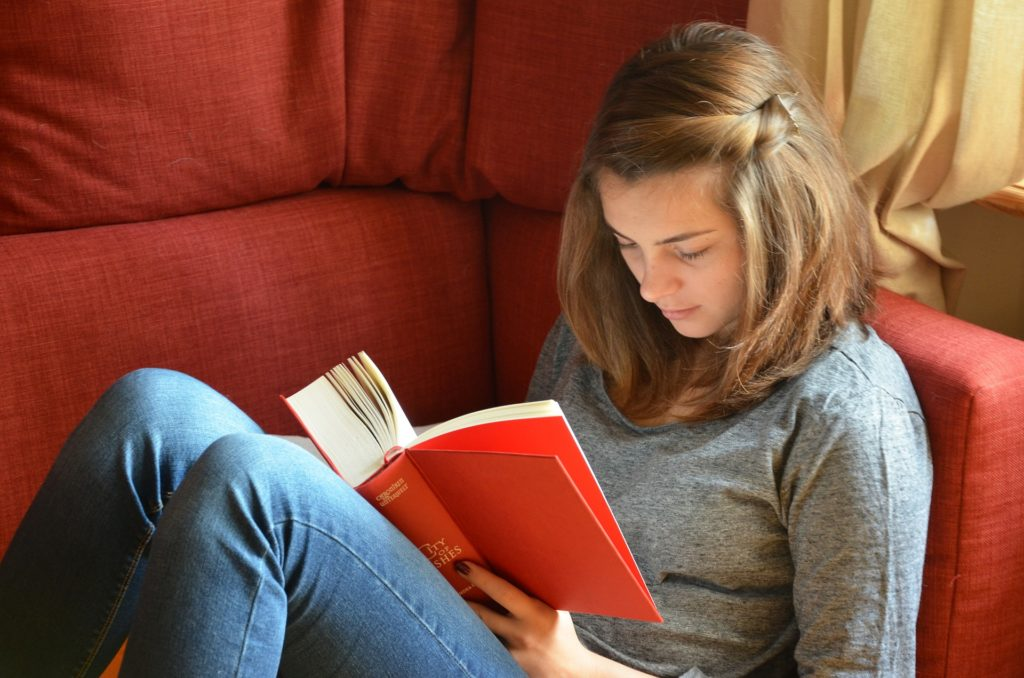 girl reading book on red couch