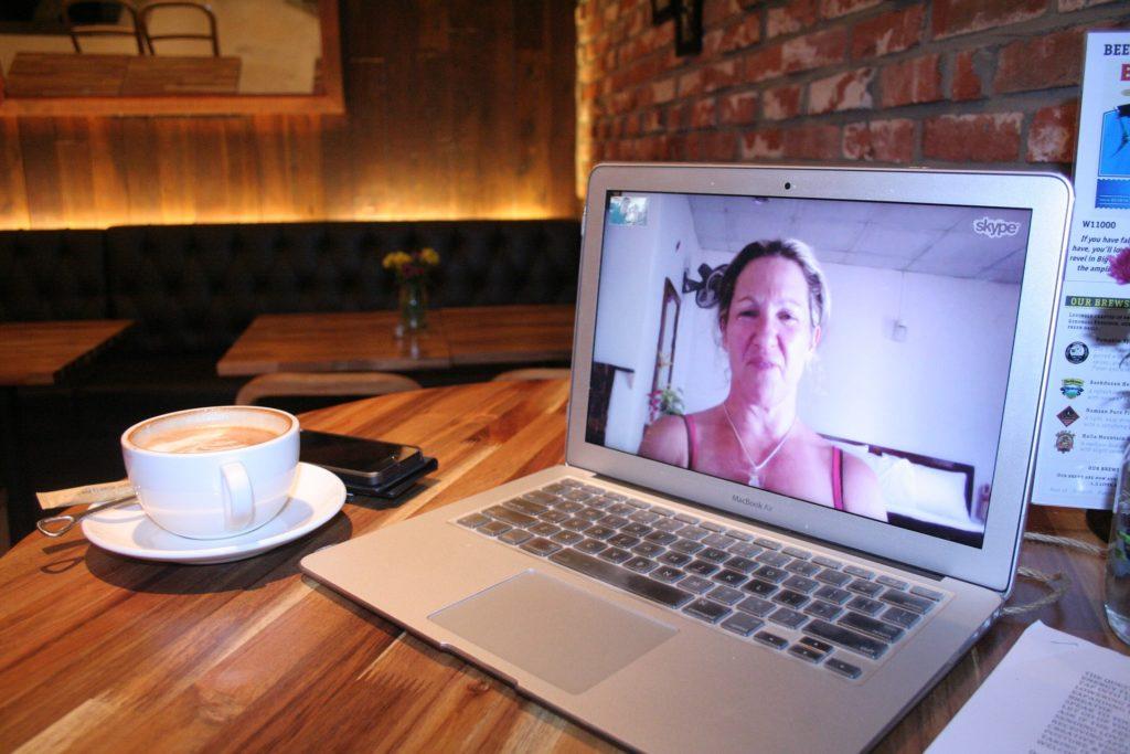 woman on skype on laptop in coffee bar