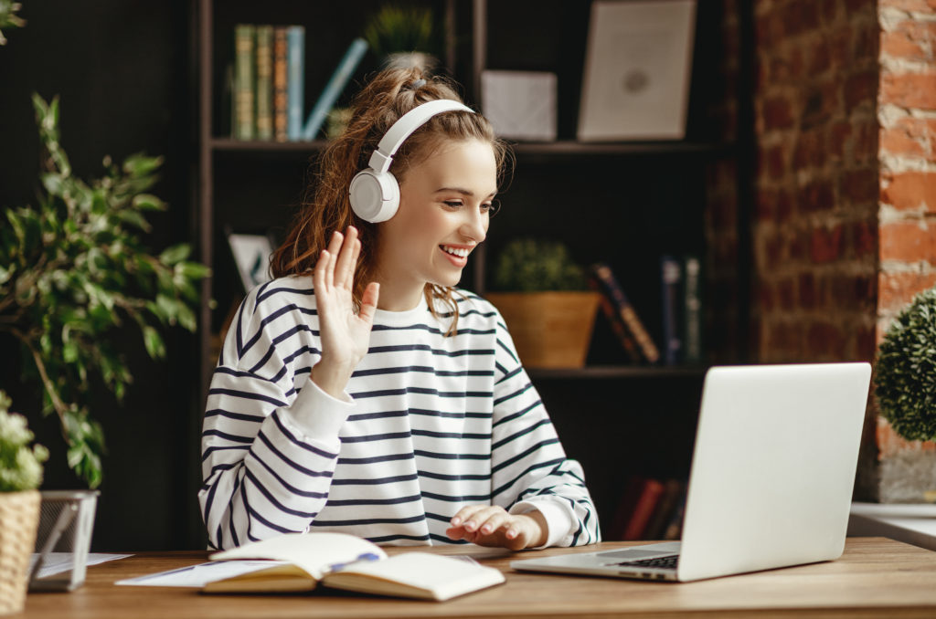 young female college student online learning waving during lecture and smiling while studying wearing wireless headphones