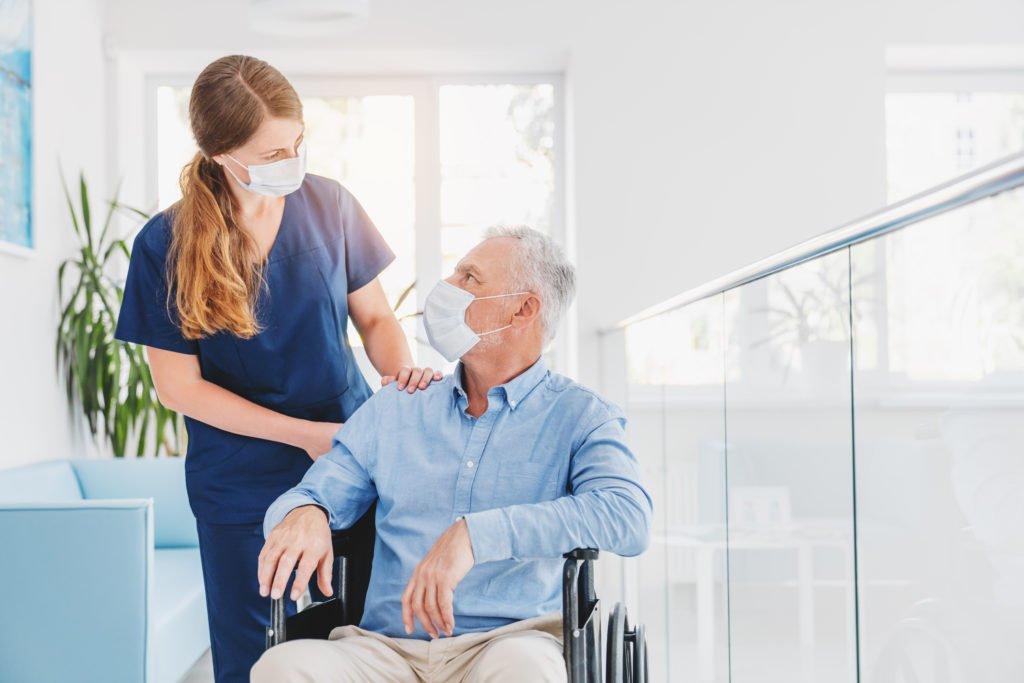 licensed practical nurse or health care assistant helping elderly man in wheelchair wearing mask