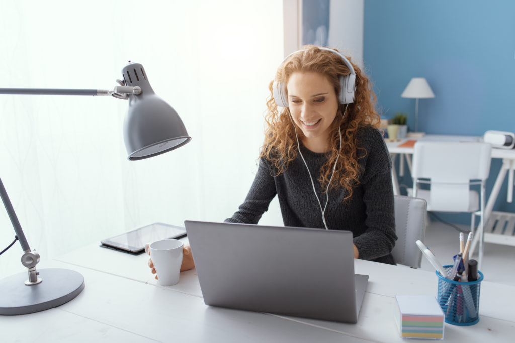 Happy young student girl wearing headphones and watching movies online, leisure and entertainment concept microsoft office courses