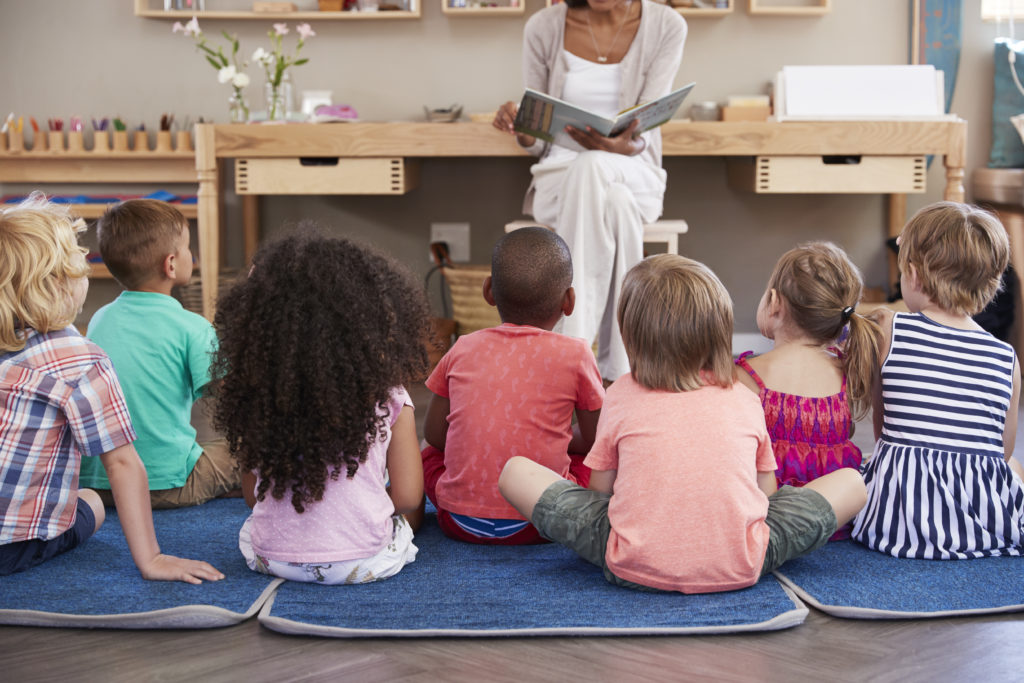 Teacher At Montessori School Reading To Children At Story Time montesssori college program macte-accredited