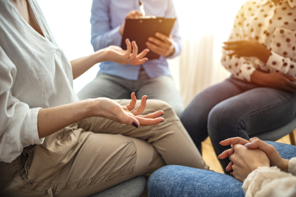 professional counselling -Emotional woman sharing her story during support session for addicts, close up on gesticulating hands. Close-up of therapist's hands explaining a problem to his patients